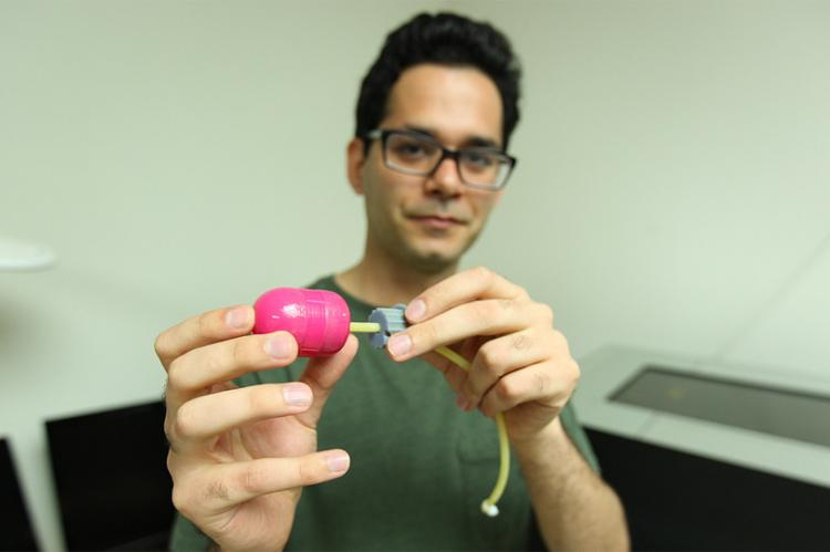 Hossein Dehghani holds a prototype of his alternative to the traditional colonoscope that physicians use when searching for pre-cancerous or cancerous polyps in the large intestine (Credit: Scott Schrage and University Communication)